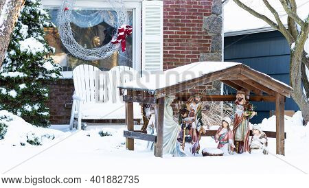 A Residential House Is Decorated For Christmas With A White Wire Wreath On The Window And A Manger S