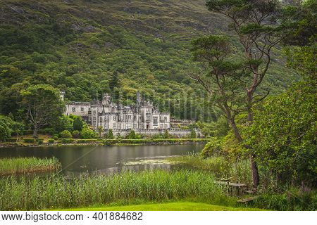 Landscape View Of Kylemore Abbey And Green Victorian Walled Garden Standing Above Blue Lake. Ireland
