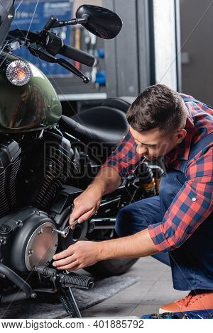 Young Mechanic Unscrewing Cap Of Motorcycle Gearbox With Socket Wrench
