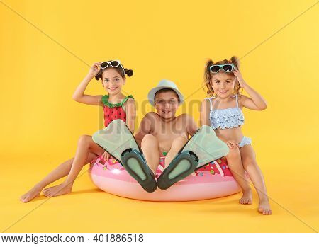 Cute Little Children In Beachwear With Bright Inflatable Ring On Yellow Background