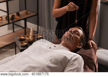 Man At Crystal Healing Session In Dark Room