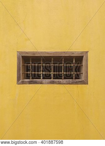 Ocher Wall With Old Small Rectangular Window With Iron Bars. Old Window On Yellow Cement Wall. Archi