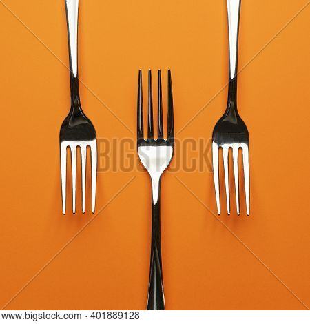 Three Forks Arranged On An Orange Surface