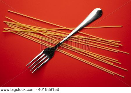 A Fork And Some Spaghetti On A Red Surface