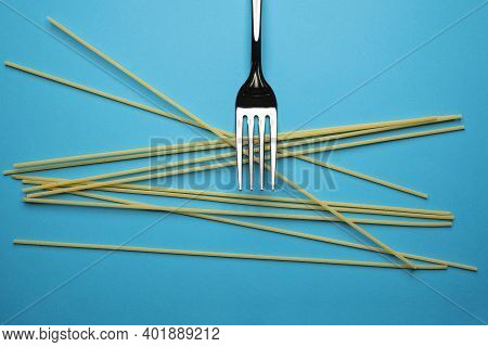 A Fork And Some Spaghetti On A Blue Surface