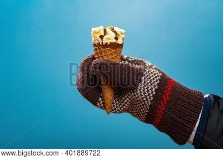 Hand With A Thick Glove And Holding A Vanilla Flavor Ice Cream On Blue