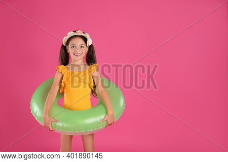 Cute Little Child In Beachwear With Bright Inflatable Ring On Pink Background. Space For Text