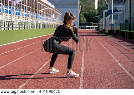 Young Adult Sporty Woman In Black Sportswear Squatting, Making Cardio Workout, Does An Exercise For