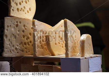 Slices Of French And Swiss Emmental Cheese, Wrapped, With Their Iconic Hole Bubbles, On Display For
