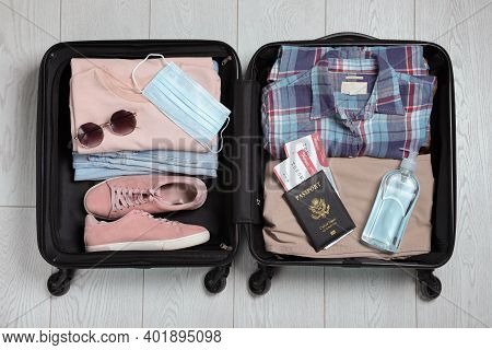 Open Suitcase With Passport, Tickets, Sanitizer And Protective Mask On Wooden Floor, Top View. Trave