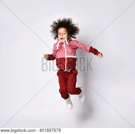 Playful Little African American Woman In Stylish Modern Red Jumpsuit Jumps High On A Gray Background
