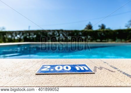 Blue Plastic Plate At The Edge Of A Swimming Pool Indicating A Depth Of 2.00 Meters