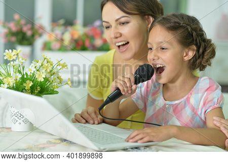 Portrait Of Smiling Mother And Daughter Singing Karaoke