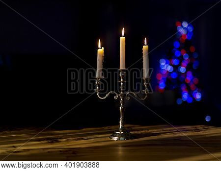 Burning Candles In Candelabra With Bright Bokeh On A Black Background,