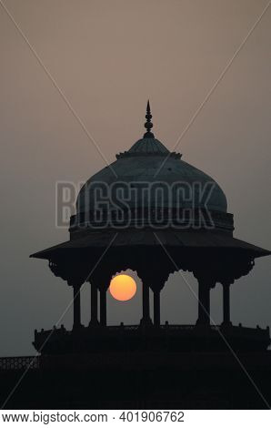The Rising Sun Is Seen As A Gold And Orange Orb Through The Pillars Of A Domed Pavillion. The Sky Is