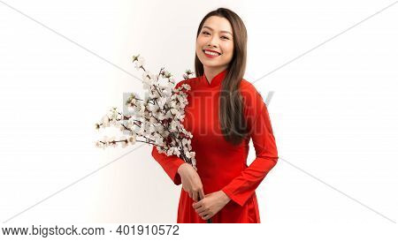 Portrait Of Asian Girl Hands Holding  Peach Blossom, In Traditional Red Ao Dai Standing On Plain Bac