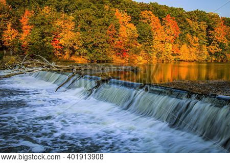 Michigan Autumn Landscape. The Grand River Surrounded By Vibrant Autumn Foliage And Small Waterfall