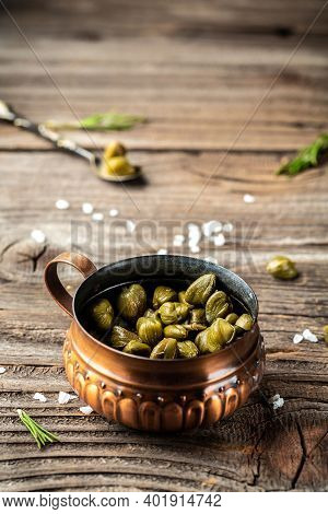 Capers Marinated Capers In A Jar On Wooden Background. Vertical Image, Place For Text. Delicious Ing
