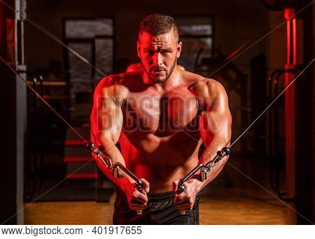 Abs And Biceps. Fitness Man Execute Exercise With Exercise-machine Cable Crossover In Gym. Handsome