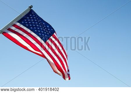 American Flag And Blue Sky. Sunlight Shines On The American Flag Set Against A Blue Sky In Horizonta