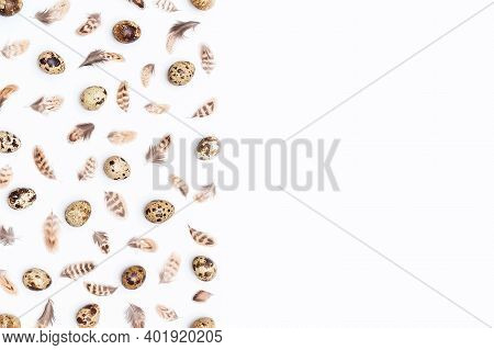 Boarder Made With Quail Eggs And Bird Feathers On A White Background. Top View Flat Lay Copy Space.