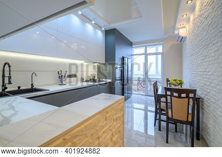 Spacious luxury white and dark grey modern kitchen interior with dining table