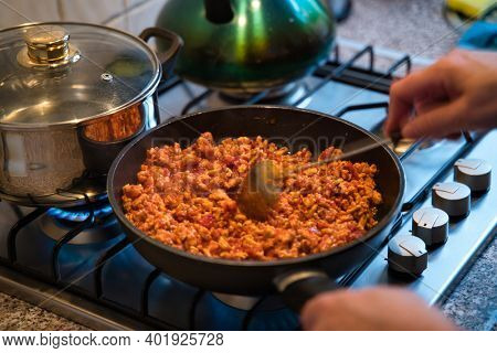 Prepping food on frying pan with silver sauce pan and kettle around