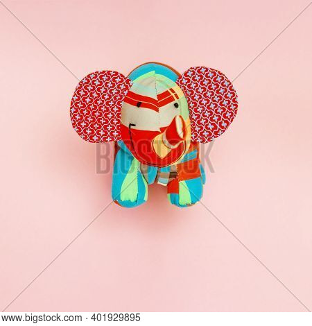 Toy Elephant Sewn From Pieces Of Colored Fabric On A Pink Background With Copy Space. Cute Animal Ma
