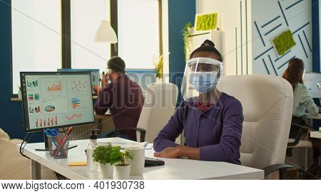 Black Employee With Visor And Protection Mask Looking Serious At Camera In New Normal Office. Multie