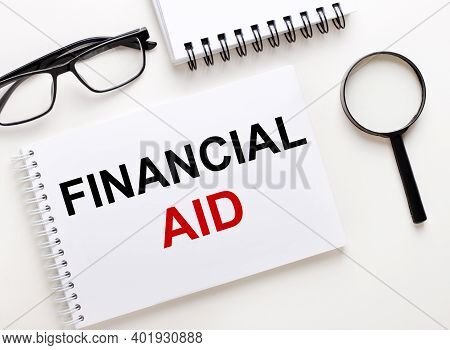 Financial Aid Is Written In A White Notebook On A Light Background Near The Notebook, Black-framed G