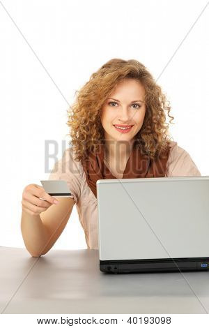 A young woman with a credit card sitting in front of a laptop, isolated on white