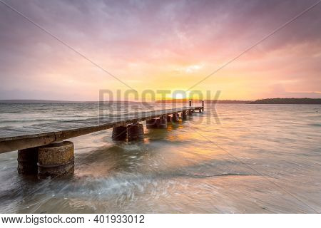 Beautiful Sunset Of Lovely Colours And A Timber Plank Jetty On Concrete Pylons On Waters Whipped Up