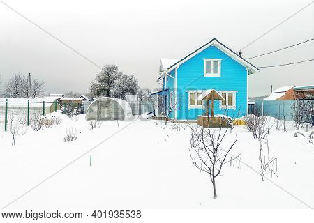 Winter Snow-covered Country Plot With Greenhouse, Wooden House With Bright Blue Facade And Snow-cove