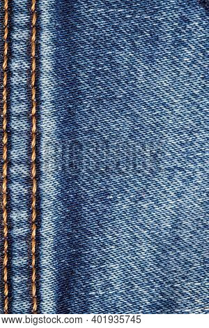 Denim Background Texture. Close-up Of Details Of Empty Blue Jeans Surface With Double Gold Colored V