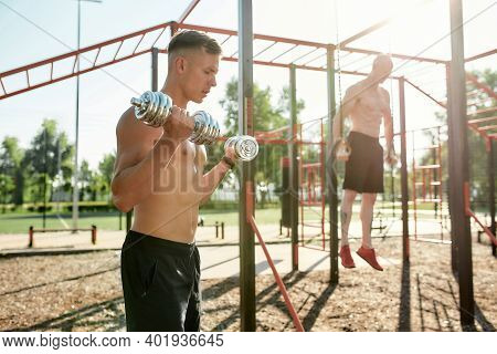 Focused Young Man With Naked Torso Exercising Outdoors With Dumbbells. Sportive Men Training Muscles