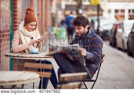 Couple On Date Sitting Outside Coffee Shop On High Street Using Mobile Phone And Reading Newspaper
