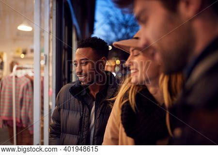Evening View Of Group Of Friends Window Shopping Looking At Display In Fashion Store