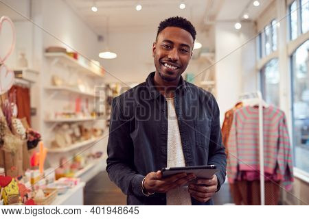 Portrait Of Male Small Business Owner Checks Stock In Shop Using Digital Tablet