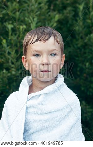 Little boy wrapped in a towel after bathing outdoors.