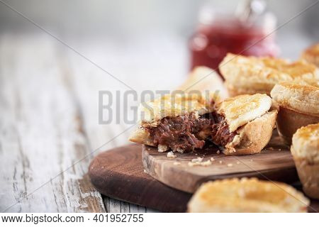 Cut Fresh Venison Meat Pies On A Rustic Wood Cutting Board With Filling Visible And Ketchup In The B