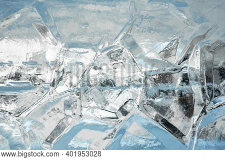 Ice Background. Full Frame Of The Textures Formed Of A Block Of Cracked Ice, On A Light Blue Backgro