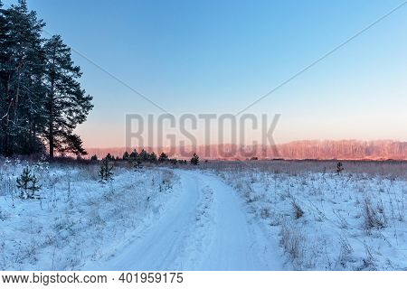 Road In A Snowy Field On A Frosty Winter Morning At Dawn