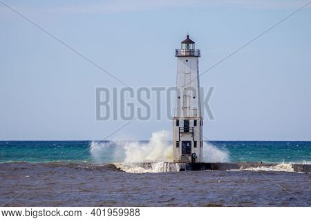 Waves On Lighthouse. Waves Crash On The Old Frankfort Lighthouse On The Coast Of Lake Michigan.