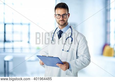 Male Doctor Standing In Doctor's Office And Working
