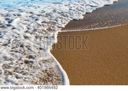 The Surf As A Natural Background: A Foamy Wave On Wet Sea Sand