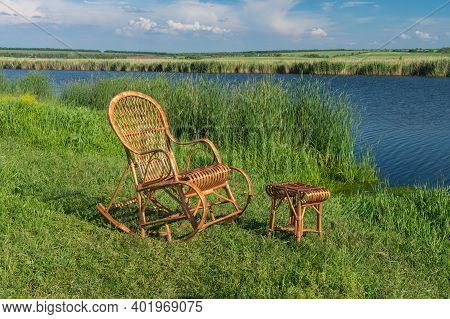 Empty Wicker Rocking-chair Standing Next To Small Wicker Hadnmade Stool,  On A Sura Riverside Waitin