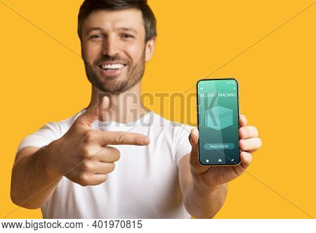 Track Your Order Online. Smiling Man Holding And Showing His Mobile Phone With Delivery Tracking Ser