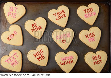 Valentines Day Concept: High angle Heart shaped sugar cookies on a baking sheet with different sayings written in icing.