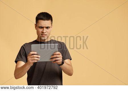 Strange Video, Shocking Information, Weird Message. Surprised And Upset Millennial Man In Brown T-sh