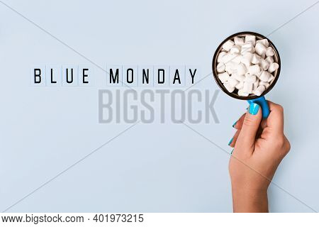 Blue Monday Text And Female Hand Holds Blue Mug With Cocoa On Blue Background. Blue Monday Concept
